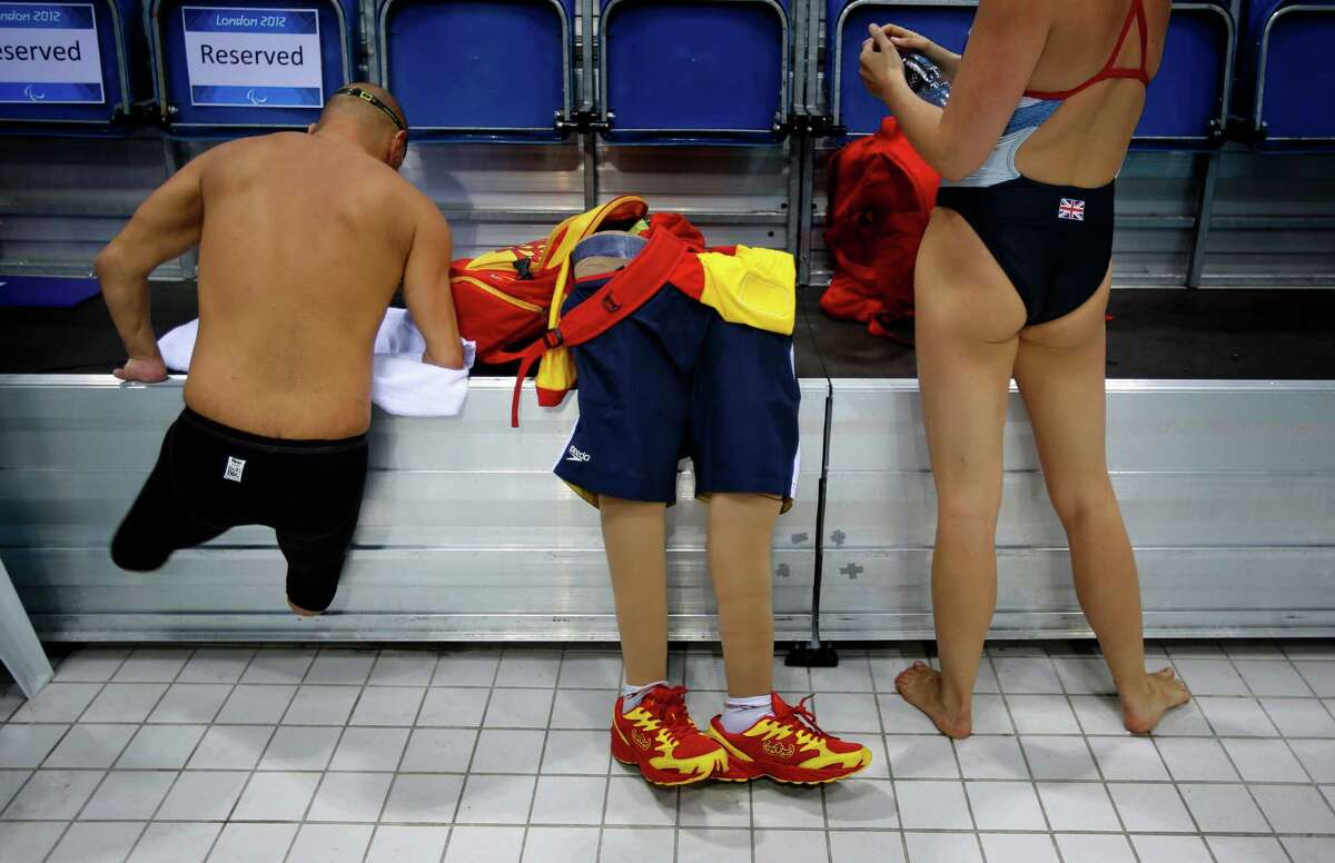 FILE - In this Aug. 31, 2012 file photo, Spain's Xabi Torres jumps next to his prosthesis as he leaves the swimming pool after training ahead of the competition at the 2012 Paralympics Olympics in London. The countdown clock for the Paralympic Games in Rio reaches 100 days on Monday with about 4,300 athletes participating, far fewer than the 10,500 in the Olympics. The Paralympic Games open Sept. 7.(AP Photo/Emilio Morenatti, File) ORG XMIT: XEM104