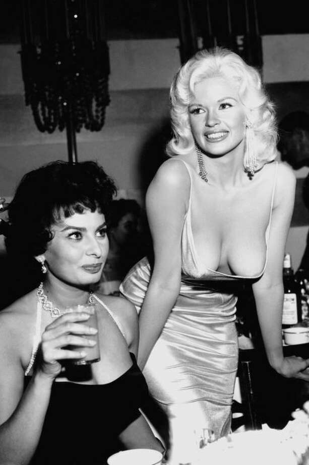 """There's a more famous photo than this from the same party in which Sophia Loren (pictured here on the left) gives Jayne Mansfield the stankiest side eye ever captured. Why the contempt? Mansfield had arrived in a dress that stole the spotlight, which was supposed to be on Loren that night. (The move was a publicity stunt; Mansfield knew that the dress would expose her boobs.) """"Look at the picture,"""" Loren recently told EW. """"Where are my eyes? I'm staring at her nipples because I am afraid they are about to come onto my plate. In my face you can see the fear. I'm so frightened that everything in her dress is going to blow — BOOM! — and spill all over the table."""" Photo: Getty Images"""