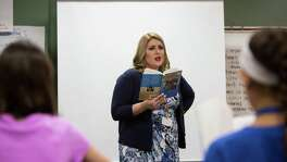 "Sara Scarborough, a sixth-grade teacher at Bleyl Middle School, reads ""The Giver"" to students last month."