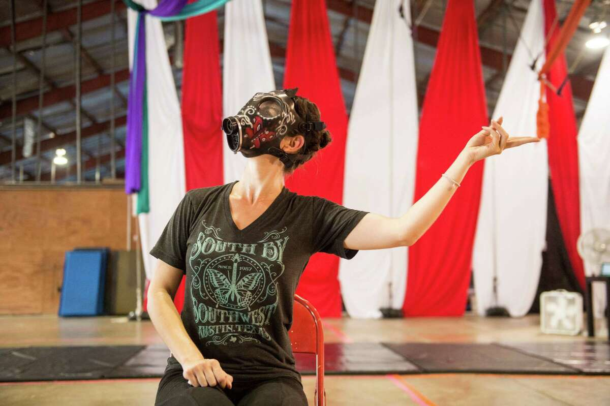 """Georgette Lockwood wars a gas mask during a """"14"""" rehearsal at Aerial Horizon on May 21."""