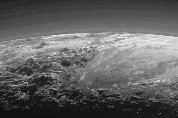 NASA's New Horizons Spacecraft snapped this photo July 14, 2015, 15 minutes after the craft's closest approach to Pluto, showing areas of icy mountains as high as 11,000 feet and areas of flat ice plains.