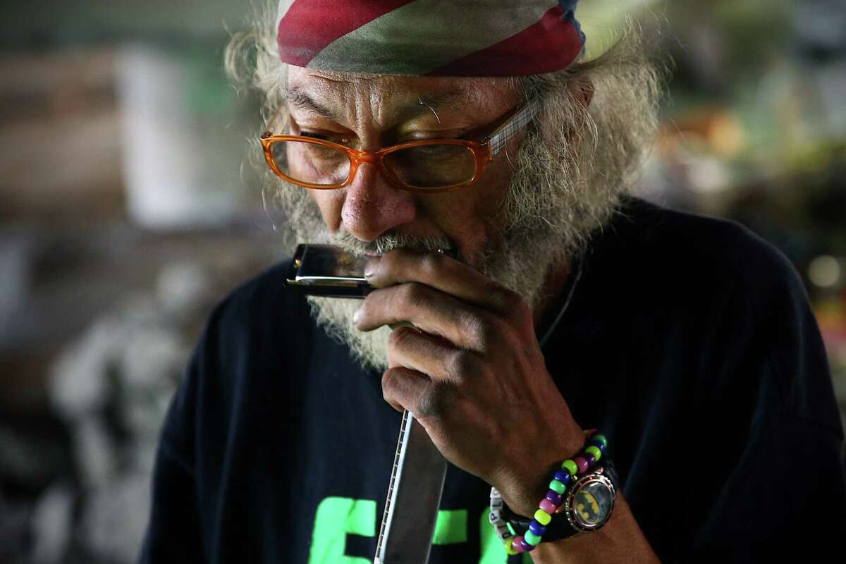 Jacob, 56, plays harmonica at his campsite. Jacob has lived in this spot for more than 10 years.