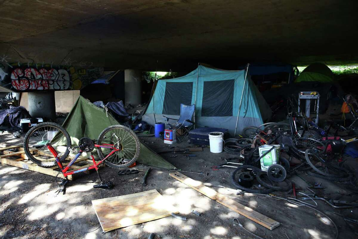 Bicycle parts and trash are scattered around a campsite in The Jungle, an area under I-5 inhabited by hundreds of Seattle's homeless, Tuesday, May 31, 2016.