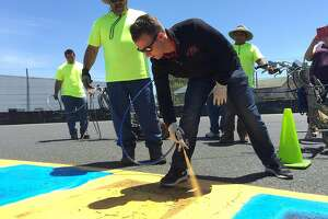 NASCAR driver AJ Allmendinger paints the curbing at Sonoma Raceway during a media event Wednesday.