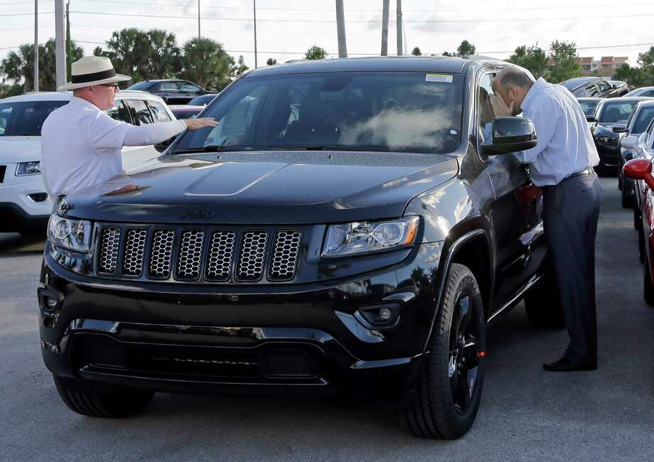 Salesman Andrew Montalvo, left, talks to a customer checking out a Grand Cherokee Limited in Doral, Fla. Photo: Alan Diaz, STF / Copyright 2016 The Associated Press. All rights reserved. This material may not be published, broadcast, rewritten or redistribu