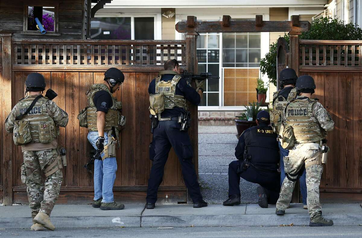 Police officers wait for a K-9 unit to do a sweep after breaching a fence door during the search for a suspect connected with the shootings of two police officers in Fremont, California, on Wednesday, June 1, 2016.