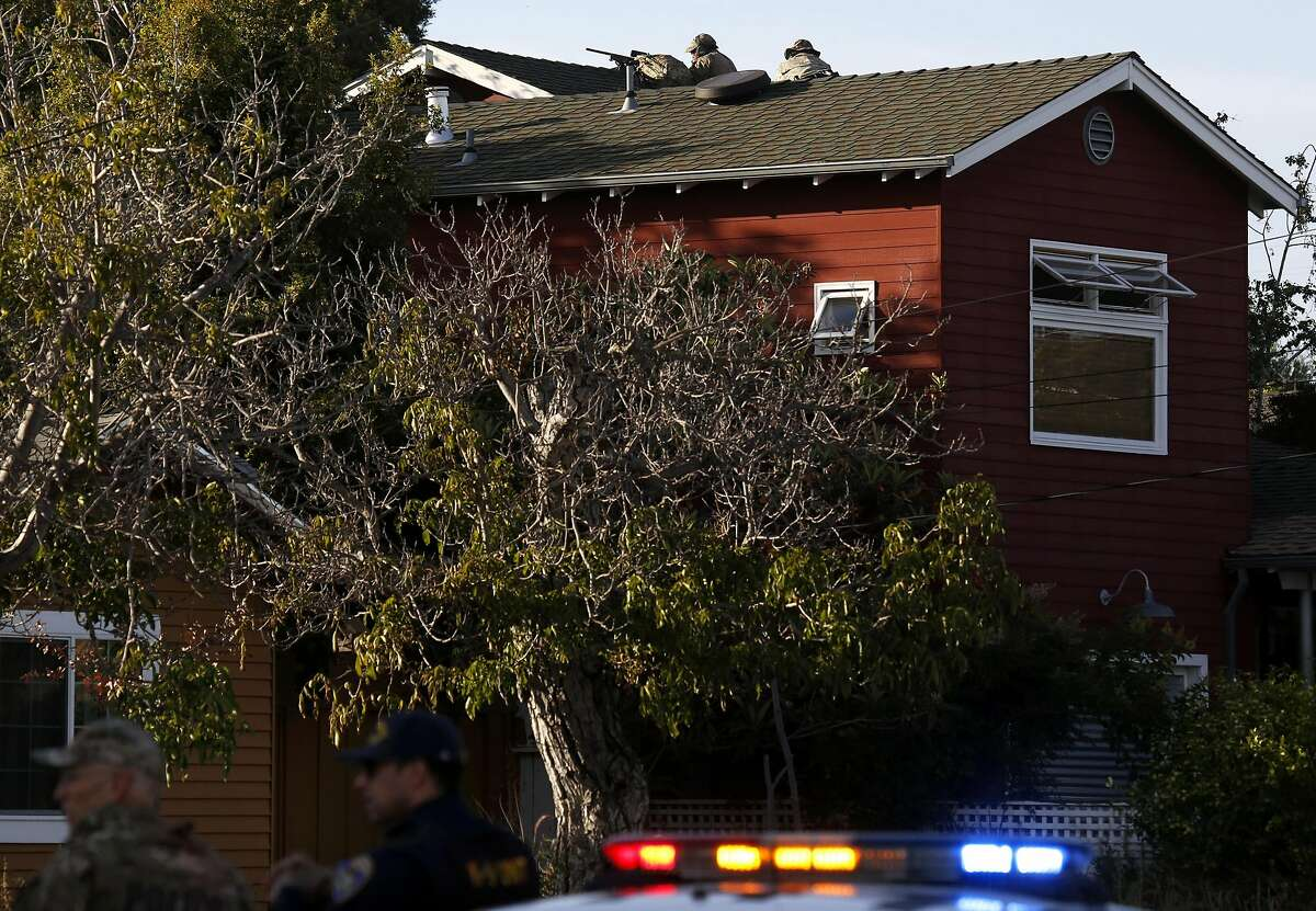 Two police officers take a position on top of a home while other officers search for a suspect in the shootings of two police officers in Fremont, California, on Wednesday, June 1, 2016.