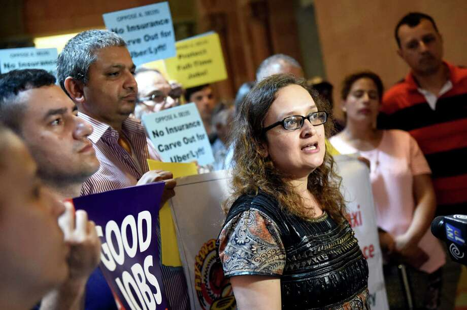 Bhairavi Desai, executive director of NY Taxi Workers Alliance, center, speaks out against opt-out insurance plan for ride-hailing apps during a rally on Wednesday, June 1, 2016, at the Capitol in Albany, N.Y. (Cindy Schultz / Times Union) Photo: Cindy Schultz / Albany Times Union