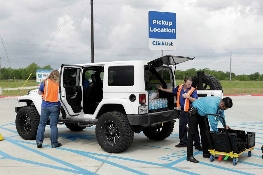 Amy Eastlick takes Andrew Garcia's payment as Paul Martinez, right, and Danny Kindred load groceries on Wednesday at Baytown's Kroger Marketplace. The store is one of four Krogers in the area to offer a pickup service. Photo: Tim Warner, Freelance / Houston Chronicle