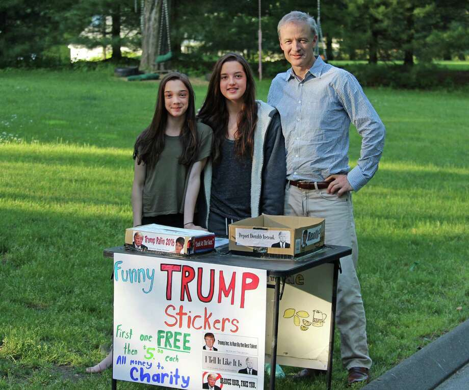 From left, Vivey, Ginger and David Ellis stand in front of their Westport home on Tuesday, selling anti-Donald Trump bumper   stickers. Photo: Chris Marquette / Hearst Connecticut Media / Westport News