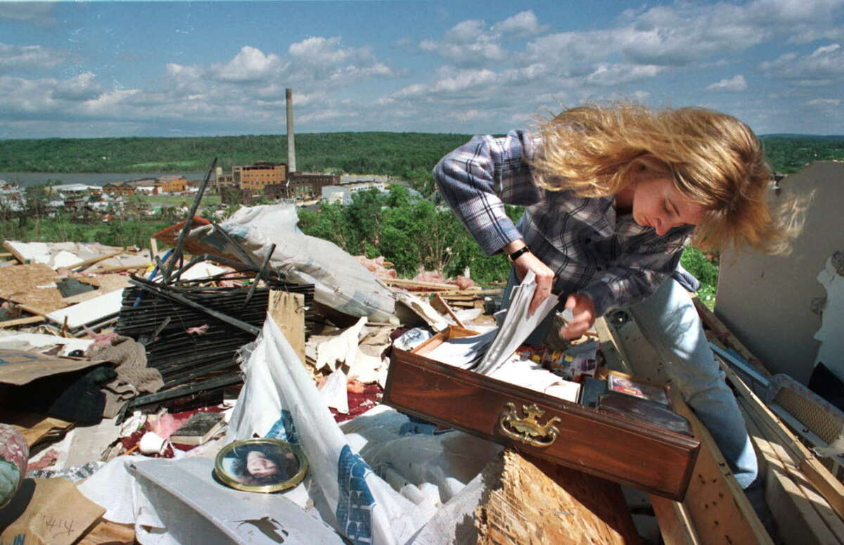 TIMES UNION PHOTO BY PAUL BUCKOWSKI -- MONDAY JUNE 1 1998 -- MECHANICVILLE, NY -- Christine Clark goes through a desk drawer in what used to be the livingroom of her home on Cannon Court in Mechicville. A tornado ripped through the area Sunday afternoon totally destroying the house