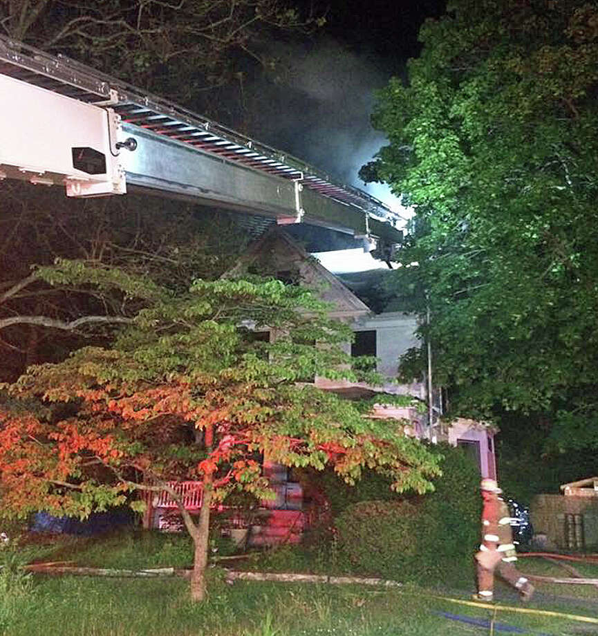 """Stratford firefighters on the scene of a house fire at 1660 Elm Street on Wednesday, June 1, 2016. On its Facebook page, firefighters posted """"we are often questioned about why we need a 95 ft aerial, since we have no buildings that tall. These photos show one of the many ways the aerial is utilized. This is a typical home, set back off the street. The aerial isn't only used for height but also for vertical reach."""" Photo: Stratford Fire Department"""