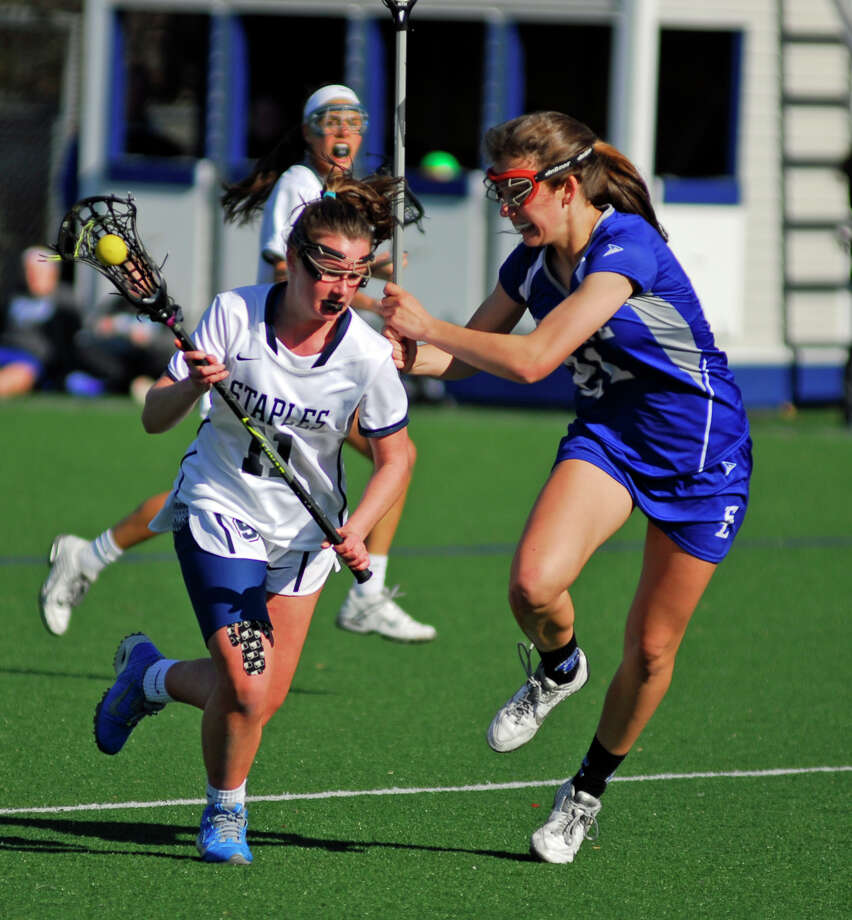 Staples' Colleen Bannon, left, is defended by Ludlowe's Amanda Schramm during a girls lacrosse game on Tuesday, April 12th, 2016. / Westport News Contributed