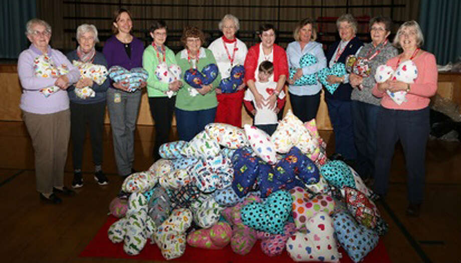 Washington Primary School recently teamed up with Matthew's Hearts of Hope for the Hug a Heart Pillow Project. Students and staff stuffed heart-shaped pillows that will delivered to children in hospitals, and local senior citizens made the final stitches on the pillows. Above are, from left to right, Doris Waldron, Nelly Condon, Principal Emily Judd, Diane Locke, Iona Douskey, Ann Dahl, Marie Hatcher, founder of Mathews Hearts of Hope with her son Matthew, Pam Collins, Dolly Whitney, Rin Dietz and Margot Finnegan. Not pictured are Maryann Lundberg and Janet Young. Photo: Courtesy Of Washington Primary School / The News-Times Contributed
