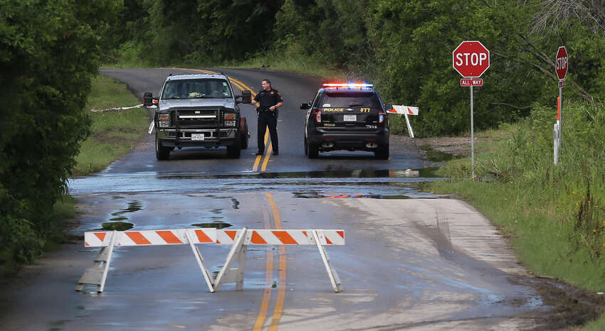 A San Antonio police officer stops motorists Thursday June 2 at Old O'Connor and Lookout roads where water is sweeping over the road after heavy rain fell in the area overnight.