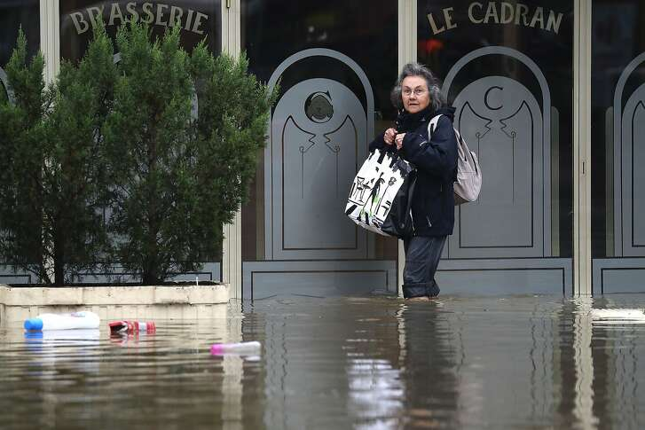 A woman holds a bag as she stands in a flooded street after the Yvette river burst its banks and forced residents to be evacuated in Longjumeau, some 20kms south of Paris, on June 2, 2016. Torrential downpours have lashed parts of northern Europe in recent days, leaving four dead in Germany, breaching the banks of the Seine in Paris and flooding rural roads and villages.