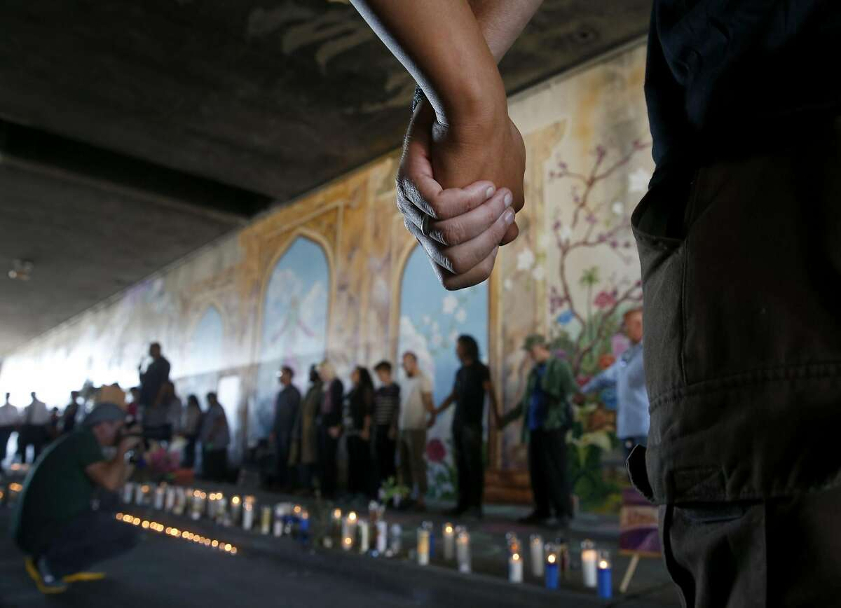 Mourners join hands during a blessing of the Superheroes Mural Project at a dedication ceremony on West Street in Oakland, Calif. on Wednesday, Oct. 21, 2015. Artist Antonio Ramos was shot and killed while working on the mural on Sept. 29.