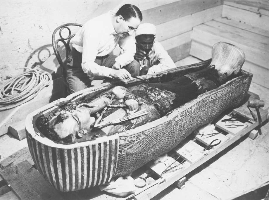 Archaeologist Howard Carter (1874-1939) examines the third mummy-shaped sarcophagus of Pharaoh Tutankhamun (or Tutankhamen, circa 1340-1323 B.C.) in the Valley of the Kings, Egypt, in this 1922 file photo. Photo: De Agostini/Getty Images