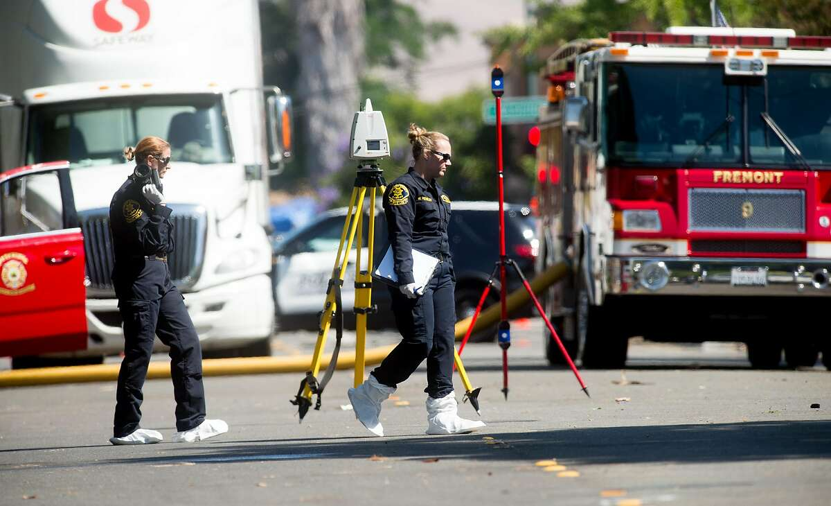 An Alameda County crime lab technician approaches a burned out home on Roberts Ave. in Fremont, Calif., on Thursday, June 2, 2016. Gerald Villabrille Jr., suspected of shooting two officers on Wednesday, was found dead inside the residence according to Fremont police.