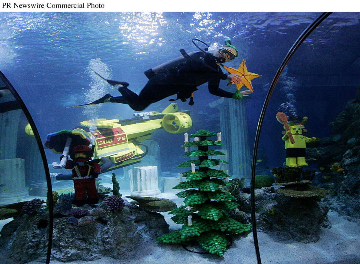 """SEA LIFE """"elves"""" Elizabeth Huber and Lance Hayes decorate a 6-foot-tall LEGO Christmas tree inside the Aquarium located next door to LEGOLAND California Resort. (PRNewsFoto/LEGOLAND(R) California Resort)"""