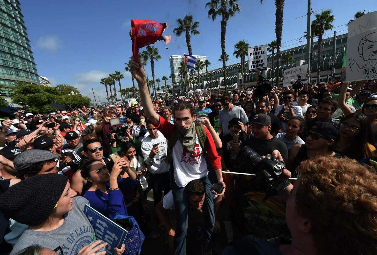 """Protesters burn a """"Make America Great Again"""" cap outside Republican presidential candidate Donald Trump's election rally event in San Diego last week. Inside, The Donald was probably smiling."""