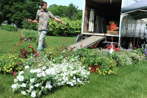 Dominic Gazy from Gazy Brothers Farm, of Oxford, unloads hanging baskets of flowering plants to be sold at the Trumbull Farmer's Market, in Trumbull, Conn. June 2, 2016. The faermer's market is open every Thursday from 3:30 to 6:30 through October 15th.
