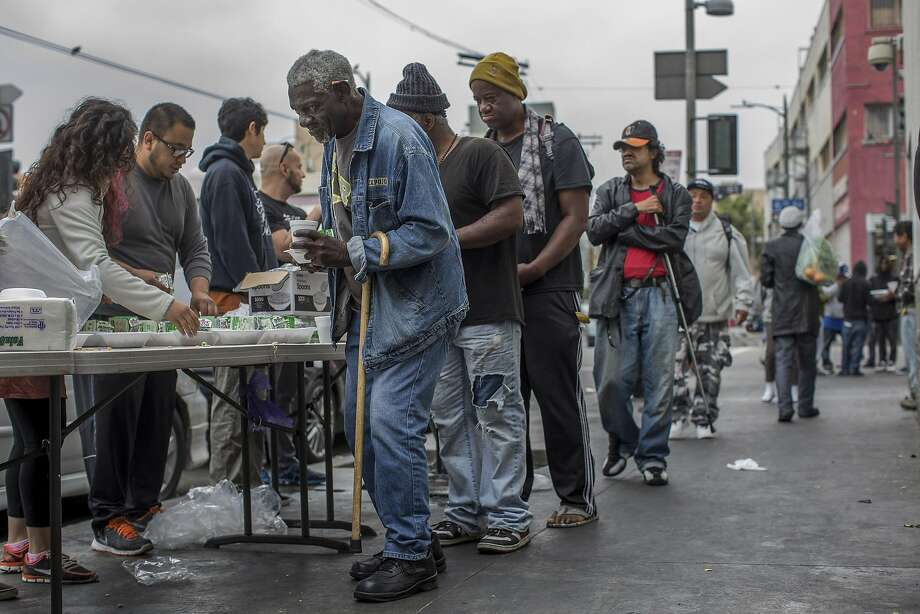 Homeless men line up for food being given out on Skid Row in downtown Los Angeles, May 15, 2016. The emergence of an older homeless population is creating daunting challenges for social service agencies and governments already struggling to fight poverty. (Monica Almeida/The New York Times) Photo: MONICA ALMEIDA, NYT