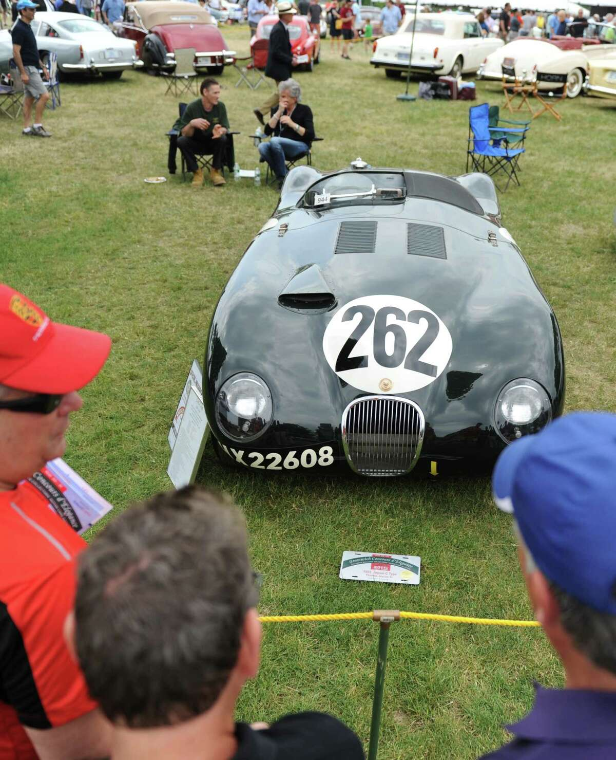 Folks look at a 1953 Jaguar C Type racecar during the second day of the Concours d'Elegance car show at Roger Sherman Baldwin Park in Greenwich, Conn. Sunday, May 31, 2015. The 20th annual show featured an immense variety of vintage and modern cars with a focus on American vehicles the first day and international vehicles the second day. The display included sports, touring and competition cars, many of which are one of a kind, limited production or custom-built for celebrities.