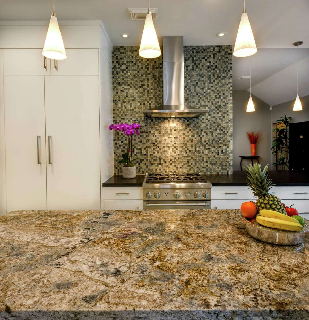 The Menefees' new kitchen island is topped with granite that's a swirl of beige, gray and blue. Coordinating glass mosaic tile lines the wall behind their Thermador range.