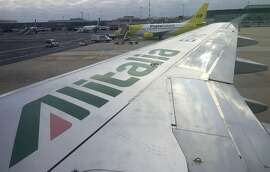 The wing of an Alitalia plane with Poste Italiane plane in Milan's Linate airport, Italy, Nov. 13, 2015. (AP Photo/Antonio Calanni)