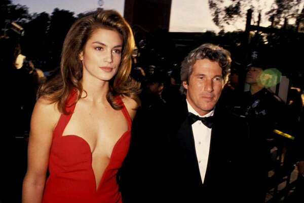 CINDY CRAWFORD, 1991 For her first red carpet with her then-boyfriend Richard Gere, supermodel Cindy Crawford dominated the red carpet at the Academy Awards. For her all-eyes-on-me moment, she wore a scarlet Versace halter dress that featured a low cut in the front...