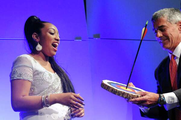 At left, Stanwich School graduating senior Niaomi King, 18, receives an arrow in a bulls-eye target from Bob DeAngelo, executive director of the YMCA of Greenwich, during the commencement at the school in Greenwich, Conn., Thursday, June 2, 2016. DeAngelo gave the commencement address at the school and awarded the arrow in the target to King after King displayed a prowess for archery on a recent trip that DeAngelo took all four graduating Stanwich School seniors on. King was the valedictorian for her class.