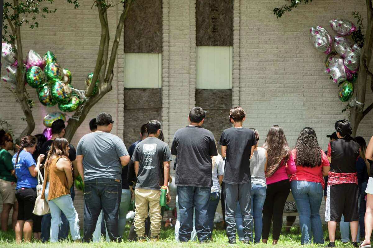 Mourners stand near a makeshift memorial for 15-year-old Karen Perez on Tuesday, May 31, 2016, in South Houston. It was early Tuesday morning when Tim Miller with Texas Equusearch confirmed Perez was found dead overnight in an abandoned apartment complex at Avenue N and 16th Street, next to South Houston High School. A juvenile suspect is in custody and murder charges are pending, the City of South Houston Police tell KHOU 11 News. ( Brett Coomer / Houston Chronicle )