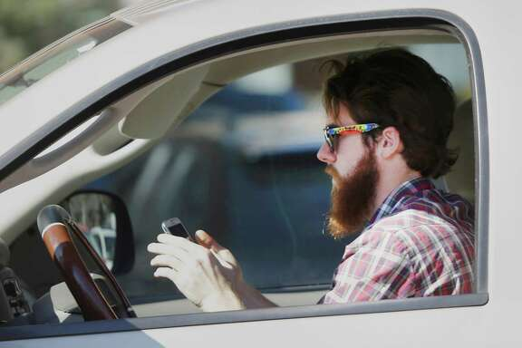 A man works his phone as he drives through traffic in Dallas. (Associated Press photo)