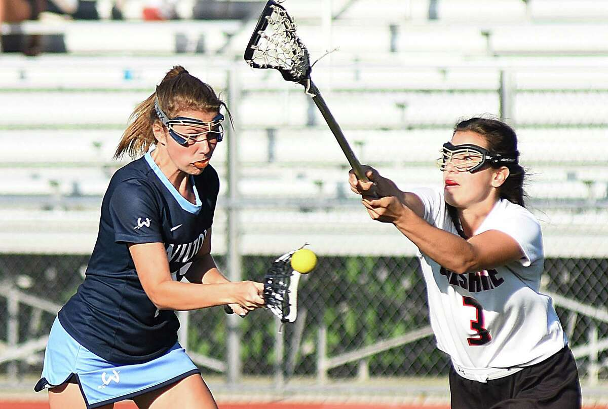Wilton's Elizabeth Armstrong, left, fires off a shot for a goal against Cheshire defender Hannah Hackett during the second half of Thursday's CIAC Class L girls lacrosse quarterfinal state tournament game at Alumni Field in Cheshire.