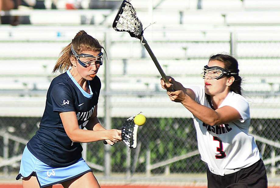 Wilton's Elizabeth Armstrong, left, fires off a shot for a goal against Cheshire defender Hannah Hackett during the second half of Thursday's CIAC Class L girls lacrosse quarterfinal state tournament game at Alumni Field in Cheshire. Photo: John Nash / Hearst Connecticut Media / Connecticut Post