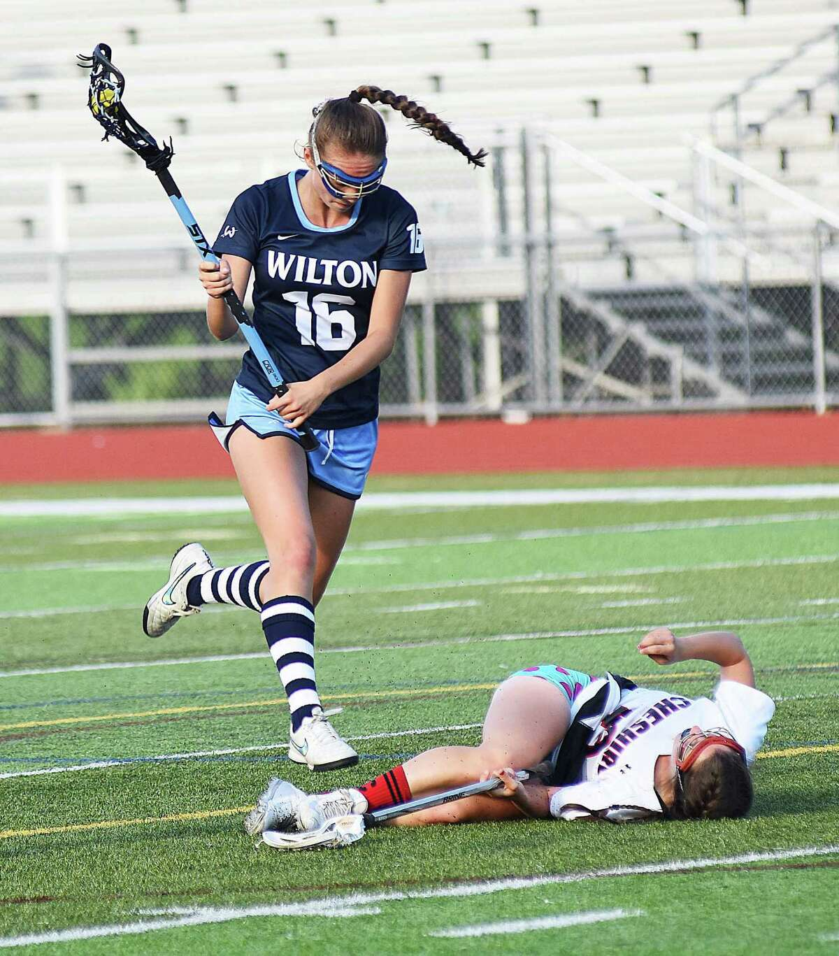 Wilton's Sydney Brandt, left, leaps over a fallen Emily Peck of Cheshire during the second half of Thursday's CIAC Class L girls lacrosse quarterfinal at Alumni Field in Cheshire.