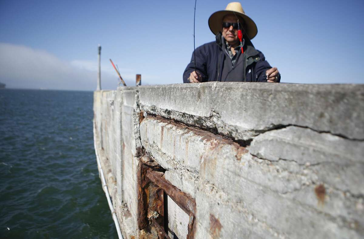"""John Macias of Concurredbegins to fish in one of the few areas not blocked off due to the piers crumbling condition on Thursday, June 2, 2016 in San Francisco, Cali. """"I hope we don't fall in"""" Macias jokes."""
