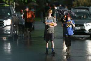 Alamo Heights fans Janis Ludwig (right) and son Adam Parker walk in the rain after Thursday's rainout at Wolff Stadium.