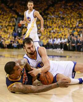 Golden State Warriors' Andrew Bogut and Cleveland Cavaliers' J.R. Smith fight for a loose ball in the first quarter during Game 1 of the NBA Finals at Oracle Arena on Thursday, June 2, 2016 in Oakland, Calif.