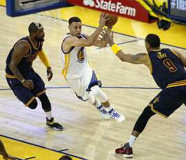Golden State Warriors' Stephen Curry drives against Cleveland Cavaliers' Kyrie Irving and Channing frtyein 1st quarter of Game 1 of NBA Finals at Oracle Arena in Oakland, Calif., on Thursday, June 2, 2016.