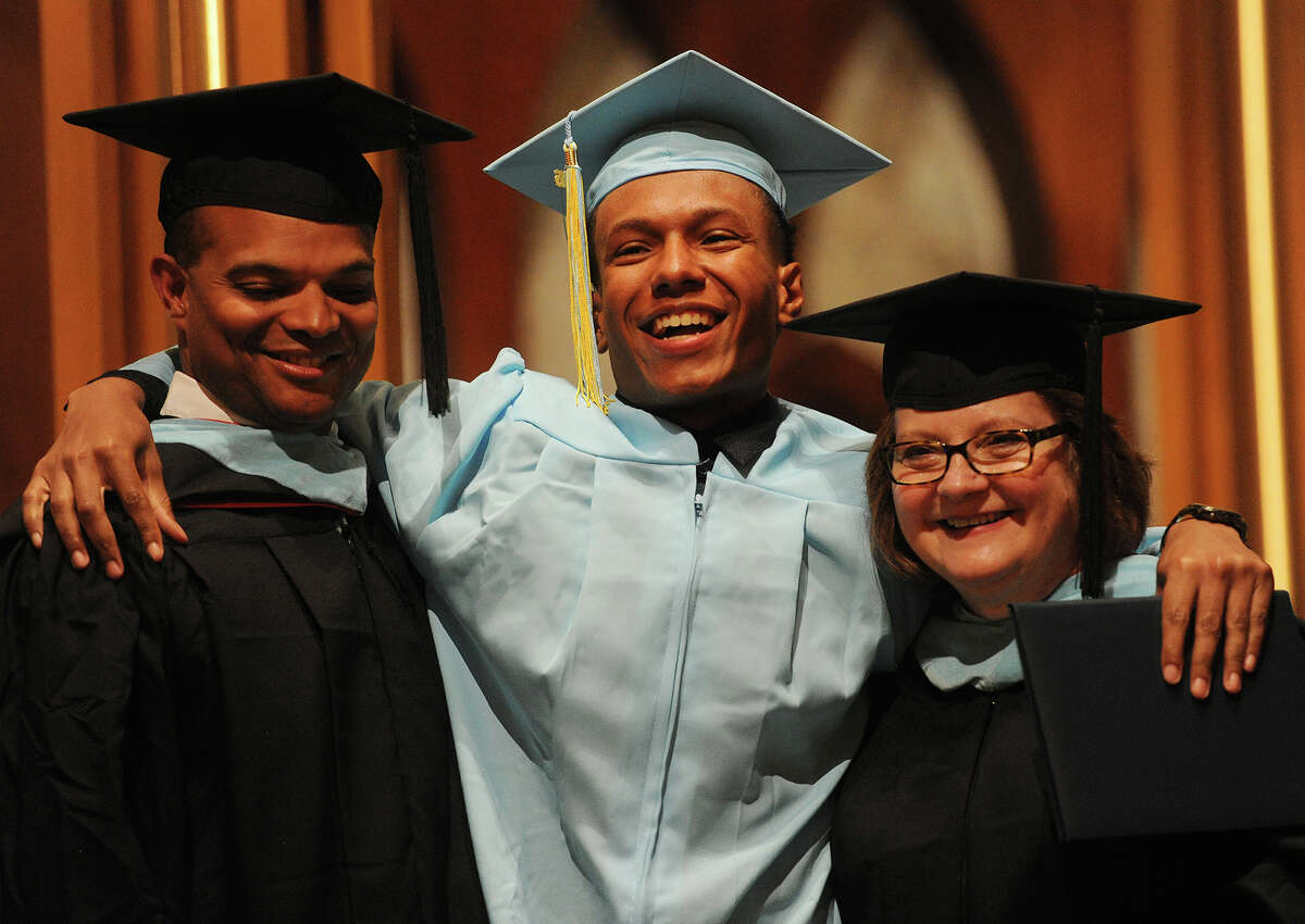 Herbert Thomas, left, poses for a picture after receiving his diploma at the Kolbe Cathedral High School graduation at Saint Augustine Cathedral in Bridgeport on Thursday.