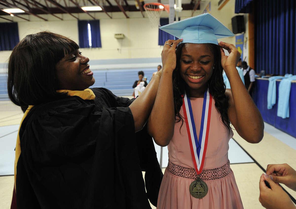 Below, Kolbe Cathedral guidance counselor Sarah Menard helps graduate Ayeisha Preston, of Bridgeport, on with her cap before graduation.