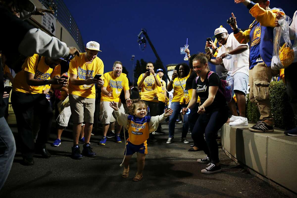 18-month-old Savannah Fredotovich dances in the middle of a dance circle as fans celebrate a Warriors victory in Game 1 of the NBA Finals outside Oracle Arena in Oakland, California, on Thursday, June 2, 2016.