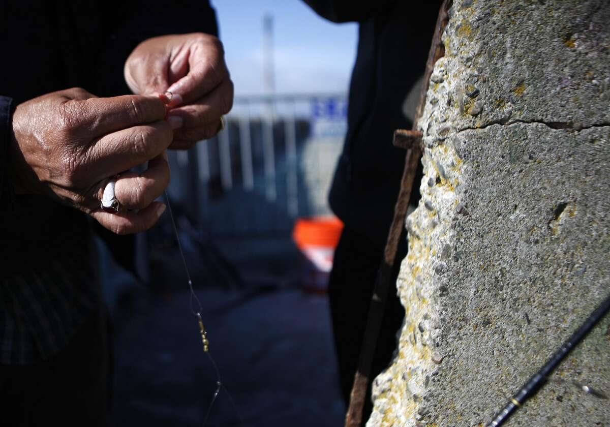 """John Macias of Concurredbegins to baits his hooks near a concrete bench with a exposed rusted rebar on Thursday, June 2, 2016 in San Francisco, Cali. """"I hope we don't fall in"""" Macias jokes."""