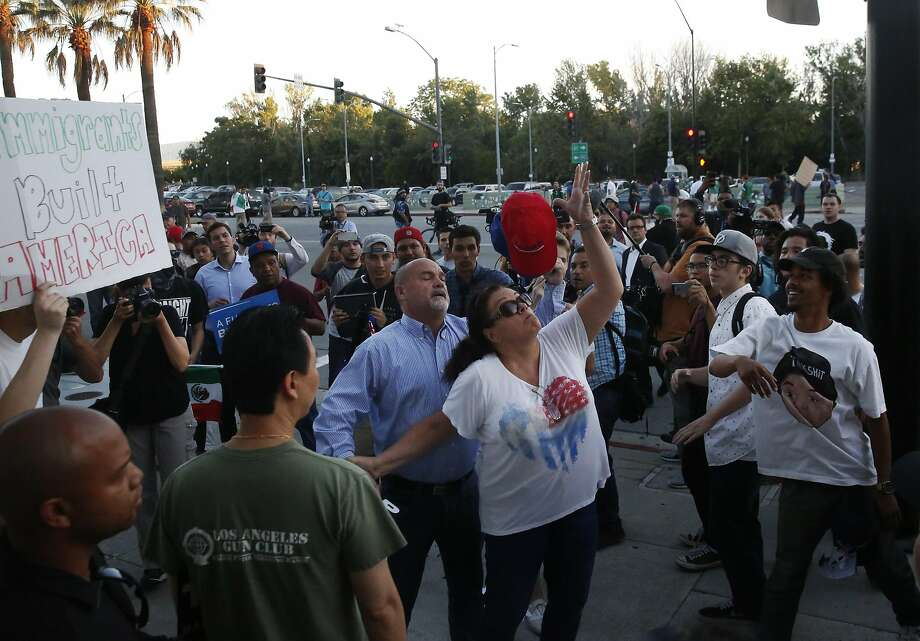 A woman grabs her hat after it was snatched while she and other Trump supporters passed protesters while leaving a rally at the San Jose Convention Center. Photo: Leah Millis, The Chronicle