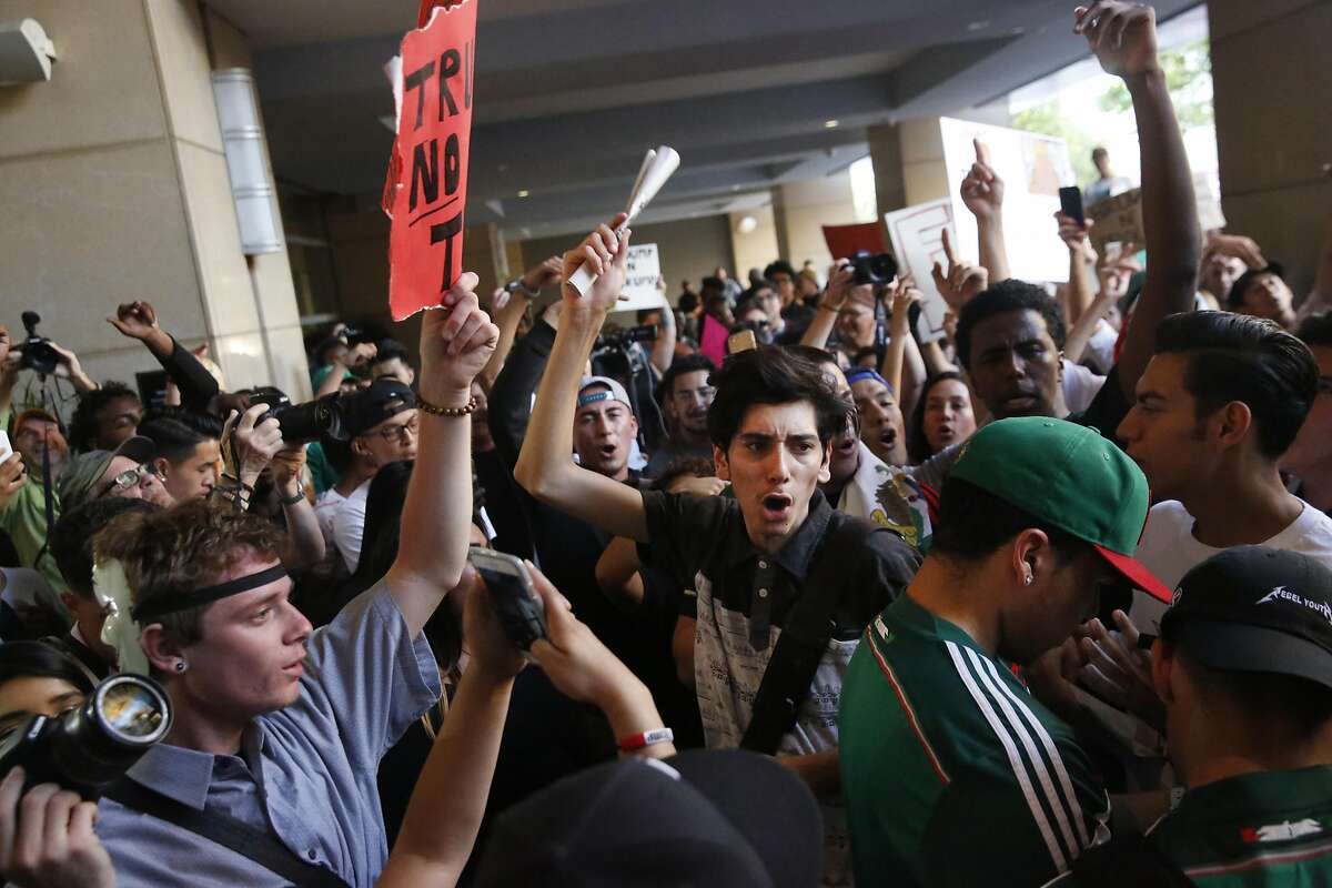 Anti-Trump protesters chant after cornering and egging a Trump supporter near the convention center where presidential candidate Donald Trump held a campaign rally June 2, 2016 in downtown San Jose, Calif.