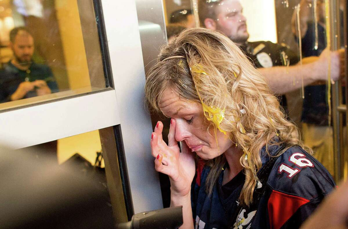 A woman wipes egg off her face after being pursued by protesters while leaving Republican presidential candidate Donald Trump's campaign rally on Thursday, June 2, 2016, in San Jose, Calif. A group of protesters attacked Trump supporters who were leaving the presidential candidate's rally in San Jose on Thursday night. A dozen or more people were punched, at least one person was pelted with an egg and Trump hats grabbed from supporters were set on fire on the ground.