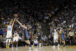 Stephen Curry (30) hits a three-pointer late in the second half as the Golden State Warriors played the Orlando Magic at Oracle Arena in Oakland, Calif., on Monday, March 7, 2016.