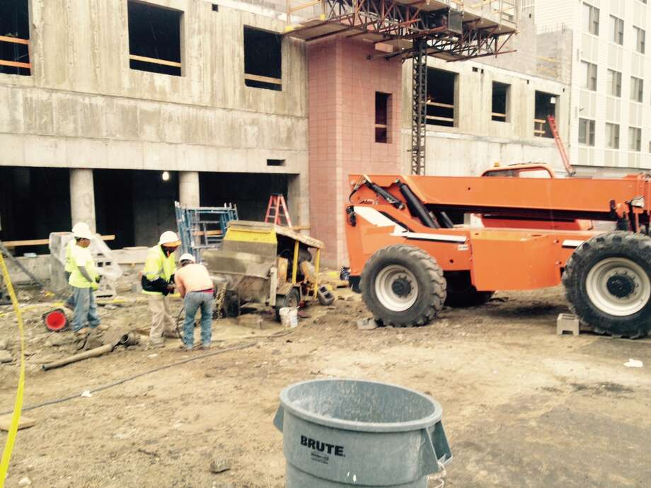 A 31-year-old construction worker was injured Friday morning when a fork lift (orange) rolled backwards and struck a liquid concrete pump (yellow), throwing the worker to the ground at the Metro Green III apartments in Stamford on June 3, 2016. Photo: / John Nickerson /TheAdvocate